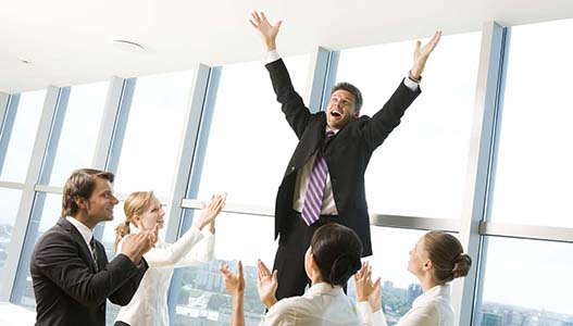 Photo of successful businessman raising his arms and shouting surrounded by his colleagues applauding   Note to inspector: the image is pre-Sept 1 2009
